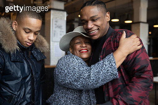 Older Black woman in a cafe having coffee with her sons - gettyimageskorea