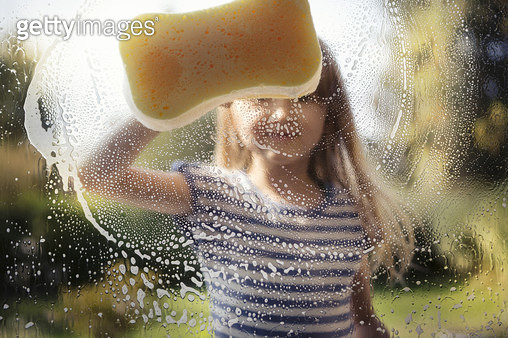 Child (6-7) washing window with sponge and soapy water, outside on a sunny day - gettyimageskorea