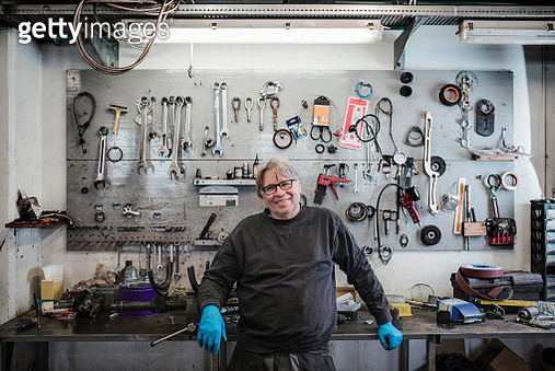 Portrait of happy mechanic standing against tools on wall at tire shop - gettyimageskorea
