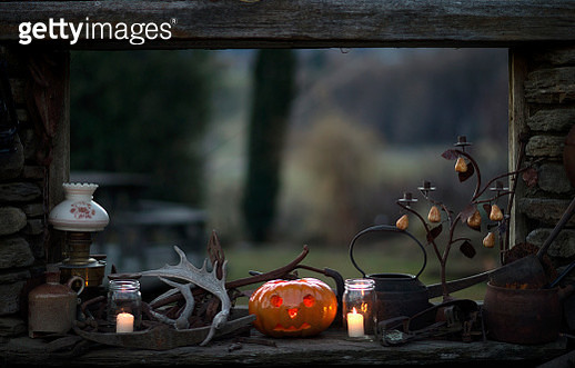 Windowsill in a rustic cabin with pumpkin, candles, candle holder, lamp and antlers. - gettyimageskorea