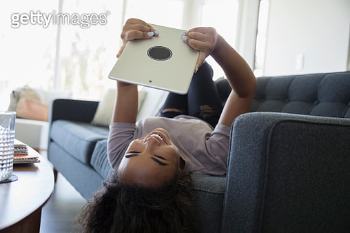 Laughing teenage girl laying on living room sofa, using digital tablet upside-down - gettyimageskorea