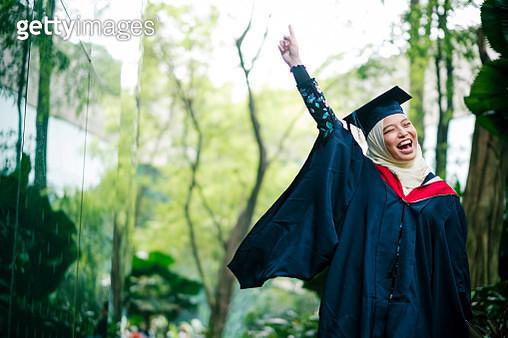Portrait of College Student Cheering on Her Graduation Day - gettyimageskorea