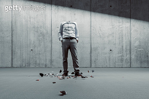 Broken businessman against concrete wall - gettyimageskorea