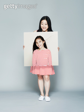 Woman holding portrait of herself as a child - gettyimageskorea