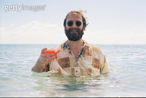 Man Drinking Cocktail In Sea - gettyimageskorea