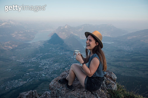 Switzerland, Grosser Mythen, happy young woman on a hiking trip sitting on a rock with a cup - gettyimageskorea
