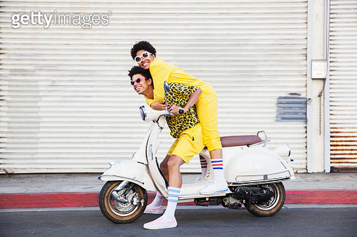 A hip young African American couple wearing bright yellow outfits posing on a scooter on a city street - gettyimageskorea