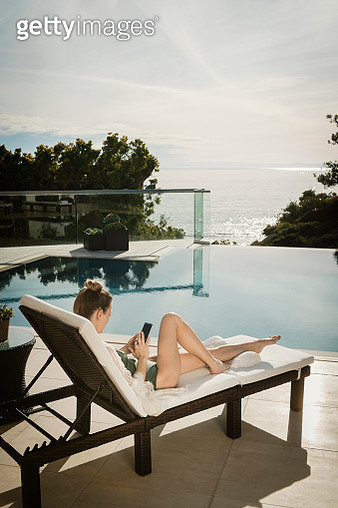 Woman relaxing by swimming pool - gettyimageskorea