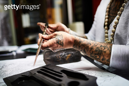 Close-up of tattooist holding tool at desk in his studio - gettyimageskorea