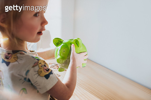 Girl shaking Piggy Bank - gettyimageskorea