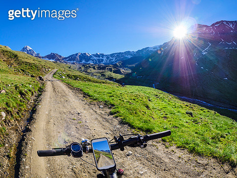 Italy, Lombardy, Cevedale Vioz mountain crest, cell phone on mountain e-bike - gettyimageskorea