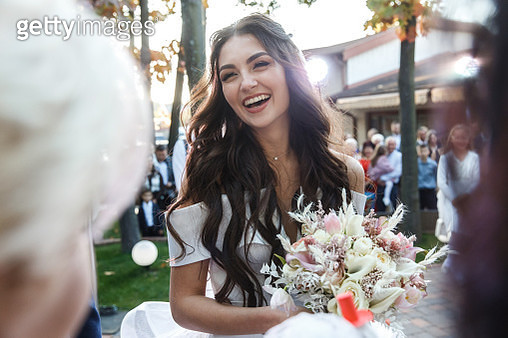 Outdoor portrait of the smiling bride among guests - gettyimageskorea