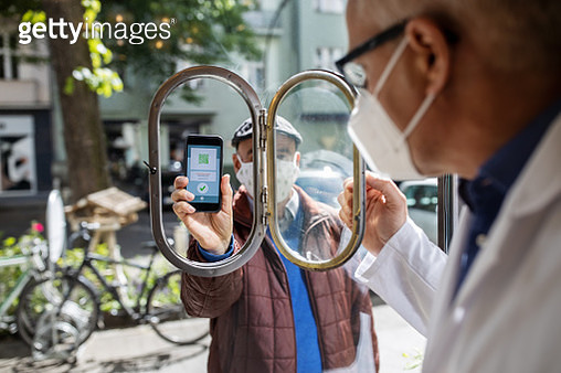 Customer showing covid-19 app to the pharmacist before entering the store - gettyimageskorea