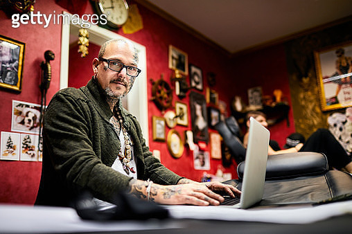 Portrait of tattooist using laptop in his studio - gettyimageskorea