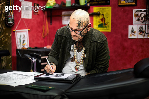 Tattooist drawing on tablet screen in his studio - gettyimageskorea