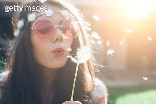Young hippie woman blowing dandelion outside - gettyimageskorea