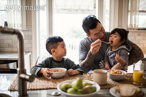 Father and children having breakfast in kitchen - gettyimageskorea