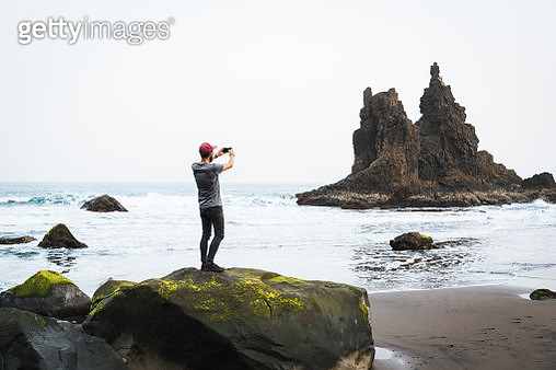 Young man stands on rock and takes photo of rocky spire in tidal flats - gettyimageskorea