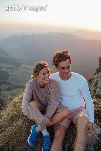 Switzerland, Grosser Mythen, happy young couple on a hiking trip having a break at sunrise - gettyimageskorea