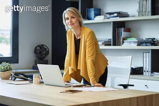 Confident businesswoman leaning on desk - gettyimageskorea