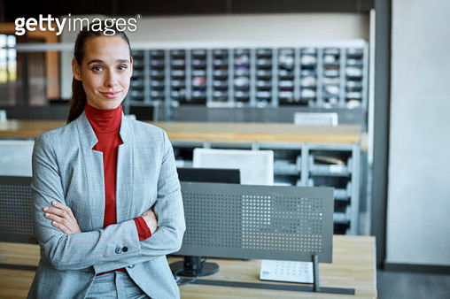 Businesswoman with arms crossed in textile factory - gettyimageskorea