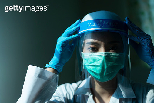 Closeup Asian female Doctor wearing face shield and PPE suit and praying for stop Coronavirus outbreak or Covid-19, Concept of Covid-19 quarantine - gettyimageskorea