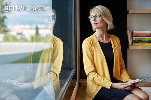 Executive with tablet PC looking through window - gettyimageskorea