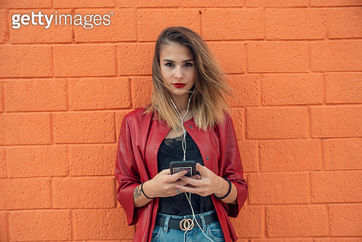 Teen Girl by red brick wall listening to music and use phone - gettyimageskorea