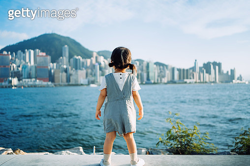 Rear view of cute little Asian girl enjoying the sun by the promenade and looking over city skyline and Victoria harbour on a lovely sunny day - gettyimageskorea