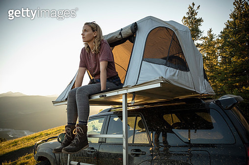 Woman relaxing at SUV rooftop tent - gettyimageskorea
