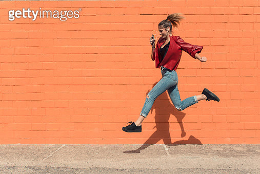 Happy young woman by red brick with headphone jumping and running to school - gettyimageskorea
