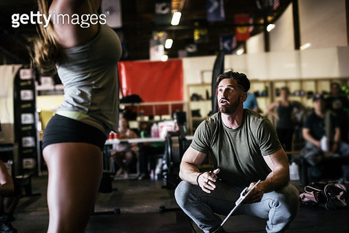 Trainer observing cross training athlete exercising in gym - gettyimageskorea