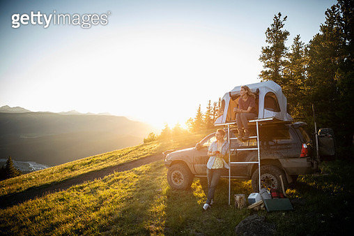 Couple camping, relaxing at SUV rooftop tent in sunny, idyllic field, Alberta, Canada - gettyimageskorea