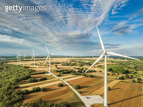 View of wind generators over cultivated land. - gettyimageskorea