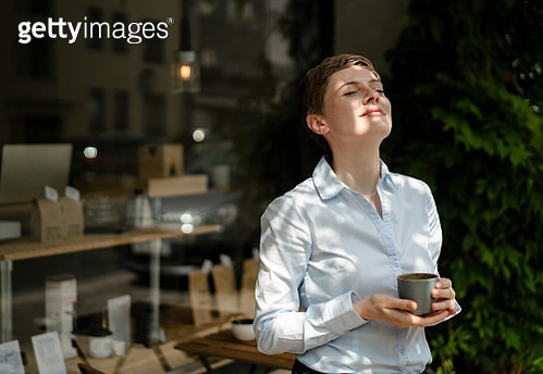 Relaxed businesswoman having a coffee at a cafe - gettyimageskorea