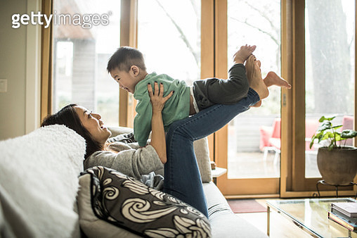 Mother playing with young son (2 yrs) on couch at home - gettyimageskorea