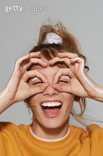 Girl holding fingers to eyes like glasses - gettyimageskorea