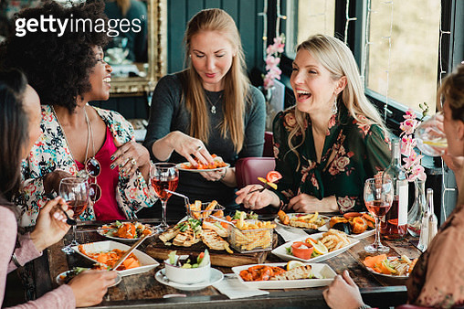 A group of women are enjoying a meal in a restaurant with rose wine. They have prawns and a sharing platter with them. - gettyimageskorea
