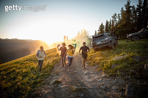 Playful friends running with smoke bombs on remote road, Alberta, Canada - gettyimageskorea