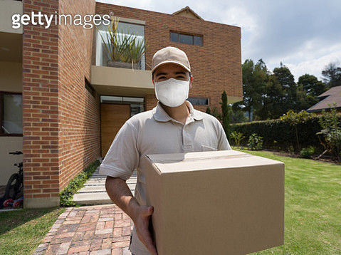 Postman delivering a parcel wearing a facemask - gettyimageskorea