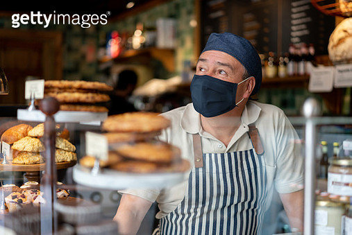 Man working at a coffee shop wearing a facemask - gettyimageskorea