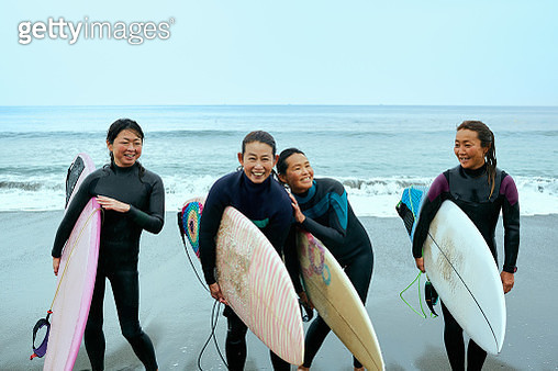 Women are laughing with a surfboard in hand at Shonan beach Japan - gettyimageskorea