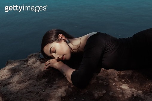 Side View Of Young Woman Sleeping By Lake On Rock - gettyimageskorea