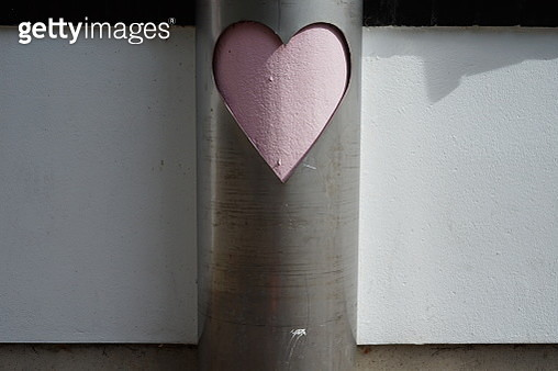 Close-Up Of Heart Shape On Metallic Pole Against Wall - gettyimageskorea