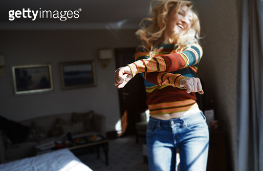 Happy woman with long hair jumping and dancing at home - gettyimageskorea