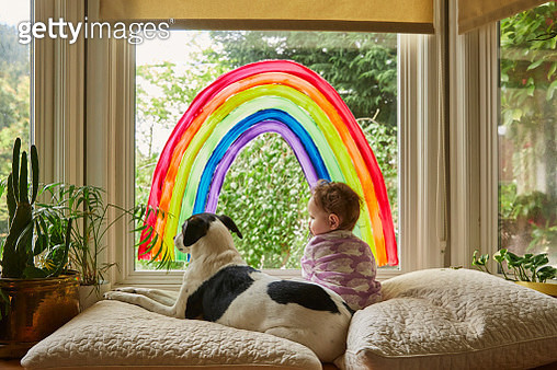 A baby sitting in a windowsill under a rainbow painted on the window, with her small dog. - gettyimageskorea