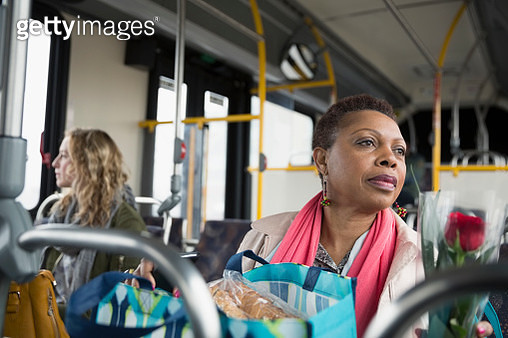 Woman with groceries riding bus - gettyimageskorea