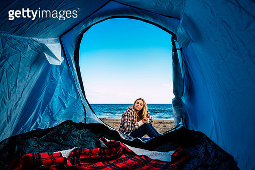 Portrait Of Woman Sitting By Tent At Beach Against Sky - gettyimageskorea