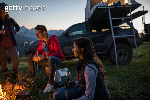 Friends drinking beer and enjoying campfire - gettyimageskorea