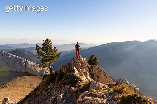 Mid adult man on mountain peak - gettyimageskorea